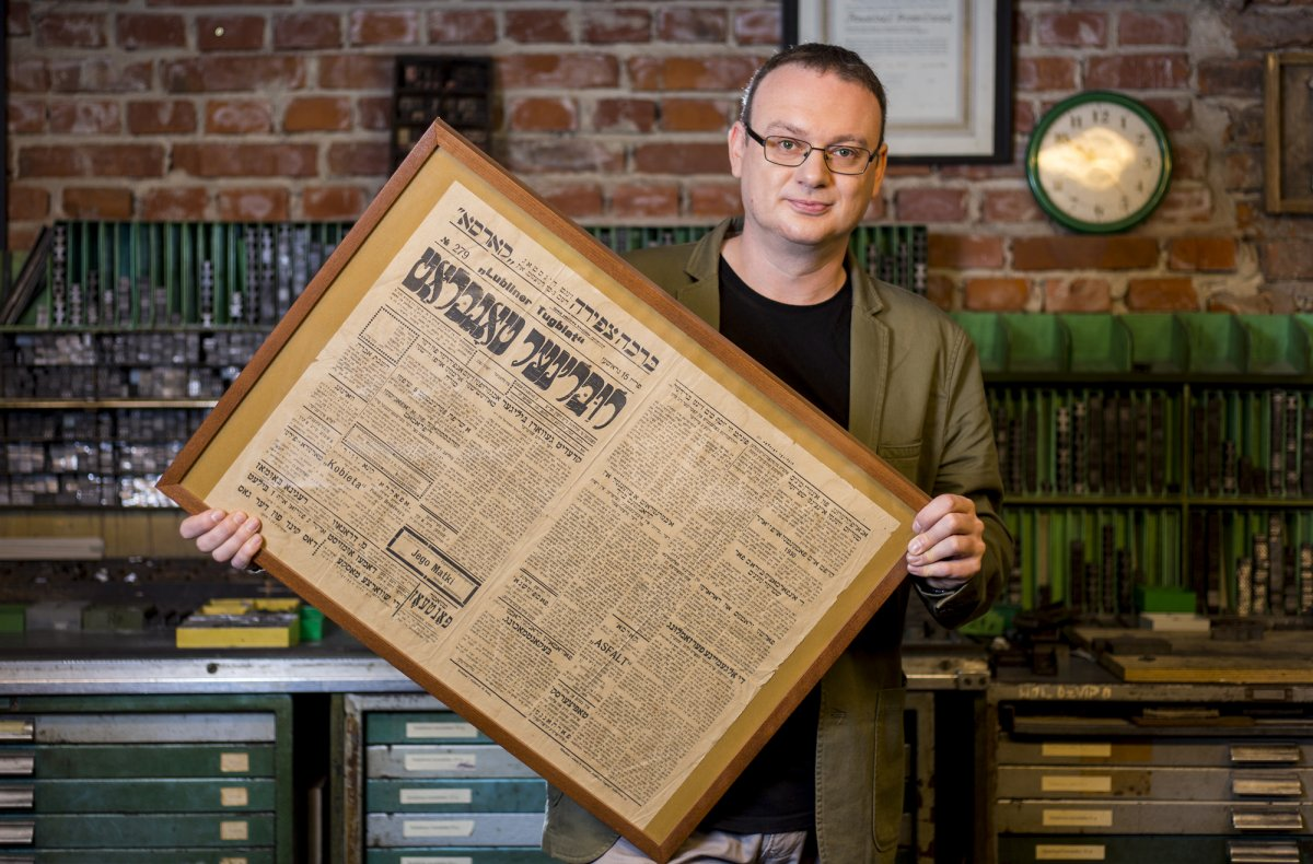Dr Adam Kopciowski presents the framed page of an old Yiddish newspaper