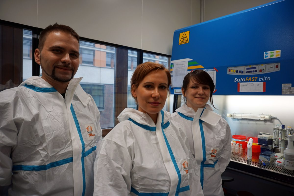 Dr hab. Krzysztof Pyrć with Dr Aleksandra Milewska and Ms Agnieszka Dąbrowska - main investigators int the project. They are standing in the laboratory on the background of research equipment, all dressed in protective suits.